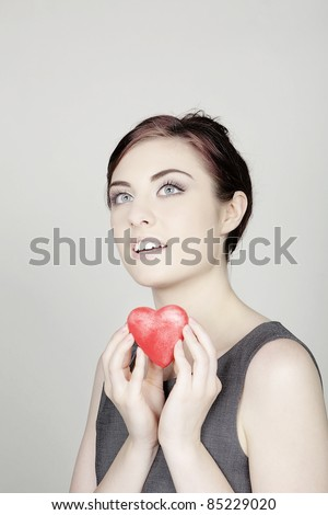 woman with a love heart shaped symbol to give to you - stock photo