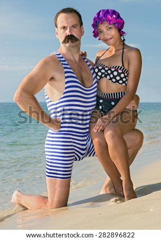 woman with a man in a retro swimsuit on the beach. A pair of retro swimwear posing on a sea beach. Vintage style couple has holiday at tropical sea. Multicultural couple on the sand beach. - stock photo