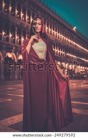Woman with a mask on San Marco square in Venice  - stock photo