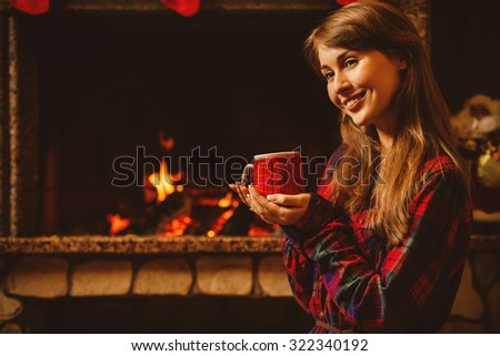 Woman with a mug by the fireplace. Young attractive woman sitting by the fireside and holding a cup with hot drink, enjoying cozy evening. Holiday time concept in a house decorated for Christmas. - stock photo