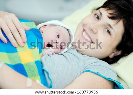 woman with a newborn baby. birth in hospital. baby after birth. child one day. - stock photo
