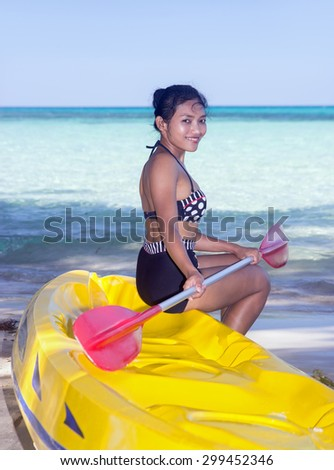 woman with a paddle sits on an inflatable boat on the sea beach - stock photo
