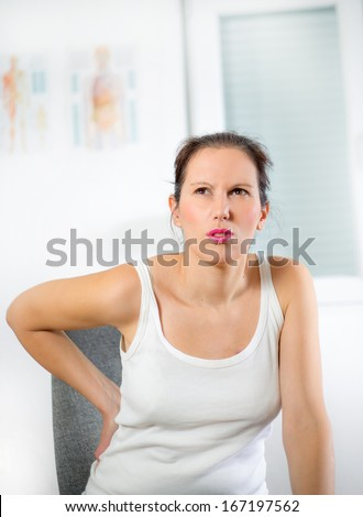 Woman with a pain in her back - stock photo
