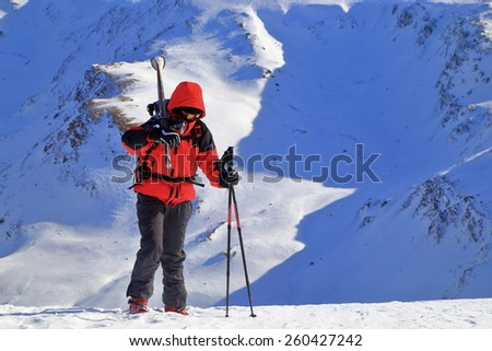 Woman with a pair of skies on the shoulders surrounded by snowy mountains - stock photo