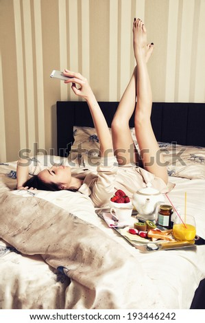 Woman with a phone in bed, photographing themselves - stock photo
