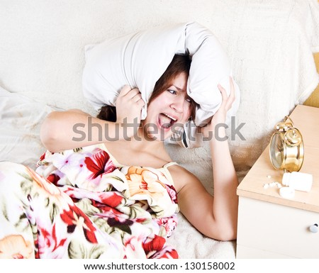 woman with a pillow on his head in horror that he could not sleep - stock photo