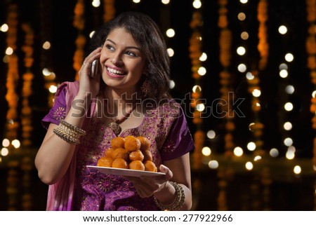 Woman with a plate of sweets talking on mobile phone - stock photo