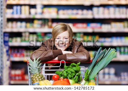 Woman with a shopping cart of fresh produce resting her chin on her hands as she leans on the cart smiling at the camera - stock photo