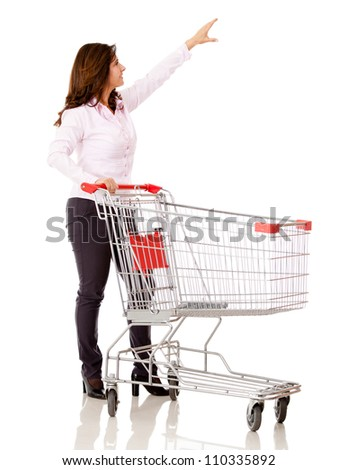 Woman with a shopping cart reaching for something - isolated over white - stock photo