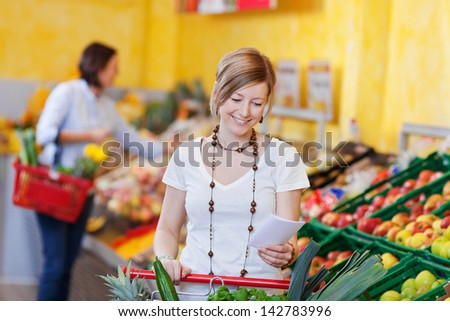 Woman with a shopping list in a supermarket standing with her trolley in the fresh produce section - stock photo