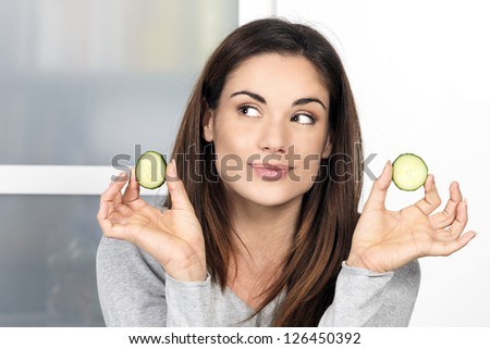 Woman with a slice of cucumber in kitchen - stock photo