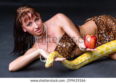 Woman with a snake holding red apple on black - stock photo