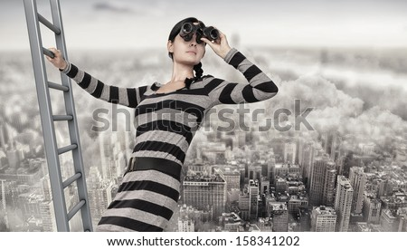 woman with a spyglass stands on top of a ladder - stock photo