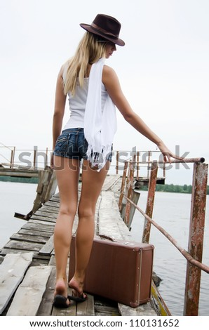 Woman with a suitcase at a pier - stock photo