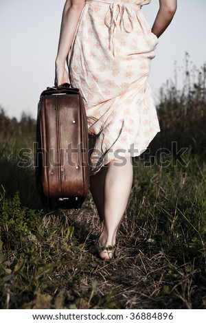 Woman with a suitcase takes on a rural road