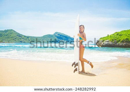 woman with a surf board on a stunning beach - stock photo