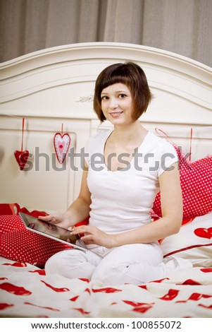 Woman with a tablet computer on the bed - stock photo