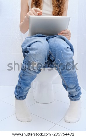 Woman with a tablet pc in a toilet. - stock photo