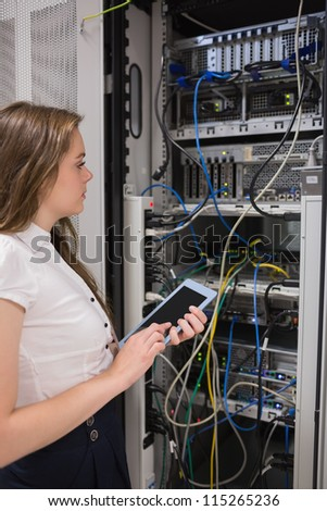 Woman with a  tablet pc looking at the servers in data center - stock photo