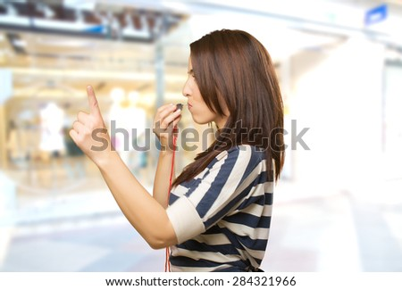 Woman with a whistle pointing with her finger. Over shopping center background