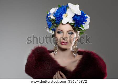 Woman with a wreath of flowers on her head in a fur coat. Young beautiful model in winter outerwear. Stylish luxury girl with a luxurious makeup