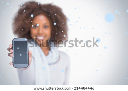 Woman with afro showing her smartphone against snow falling - stock photo