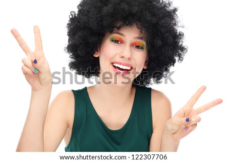 Woman with afro showing peace sign - stock photo