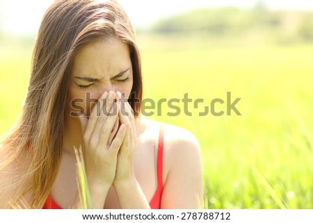 Woman with allergy coughing in a green color field in summer