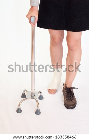 Woman with an injured leg holding a quad stick, isolated - stock photo