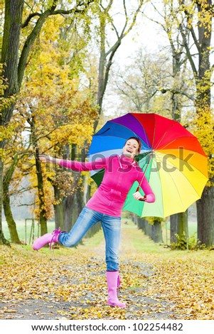 woman with an umbrella in autumnal alley - stock photo