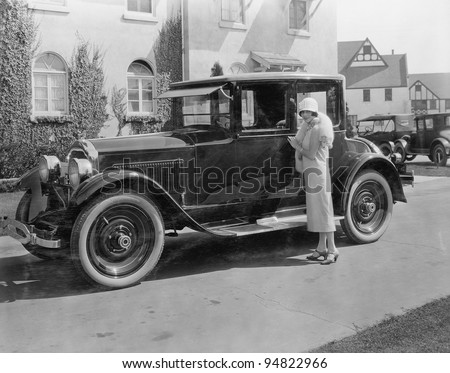 Woman with antique car outside large house