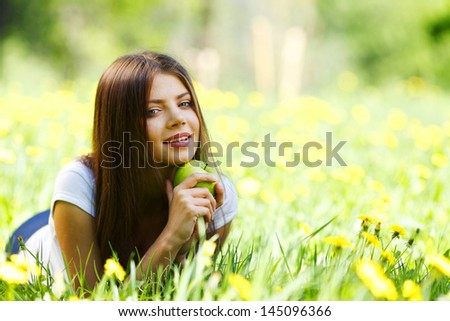 Woman with apple laying on green grass