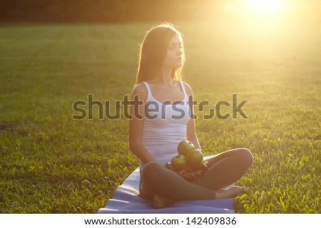 woman with apples on green grass. Outdoor - stock photo