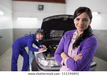 Woman with arms crossed next to a car in a garage - stock photo
