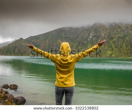 Woman with arms raisaed feeling the nature and enjoying the lake view