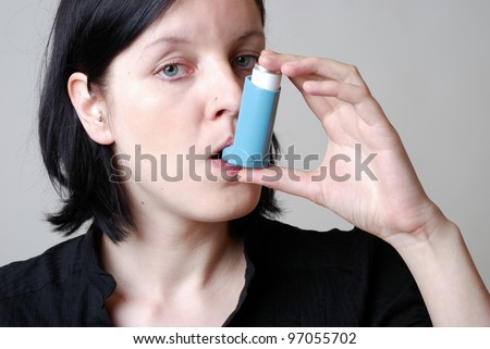 woman with asthma inhaler - stock photo