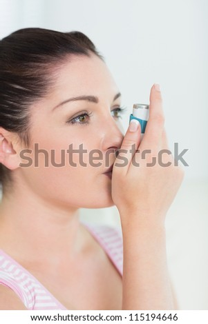 Woman with asthma using an asthma inhaler for preventing attacks - stock photo