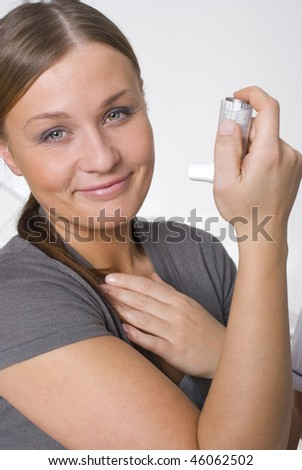 Woman with asthma using inhaler - stock photo