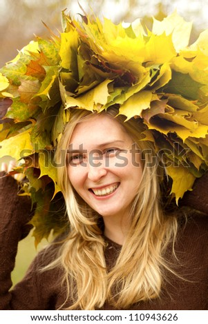 Woman with autumn wreath looking on camera outdoors