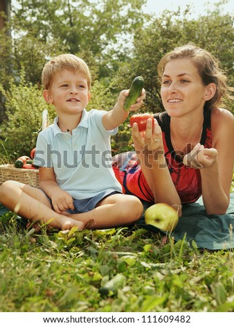 woman with baby on picnic/Young woman with a little son sitting on the grass and eat vegetables. Sunny summer day