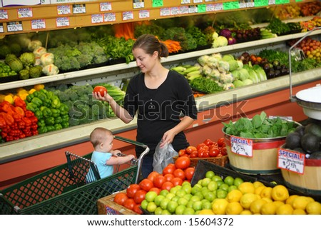 Woman with baby shopping in grocery store - stock photo