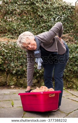 woman with back pain, trying to carry weight - stock photo