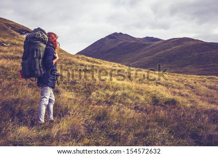 Woman with backpack about to climb mountain - stock photo