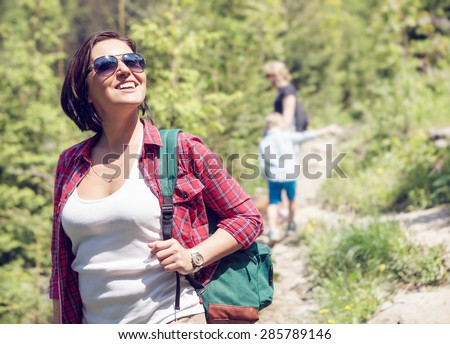 Woman with backpack in forest at the sunny day - stock photo