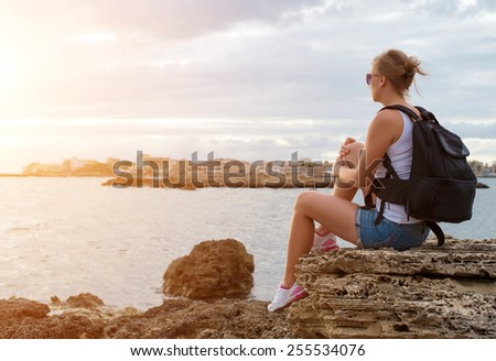 Woman with backpack relaxing near the sea. - stock photo