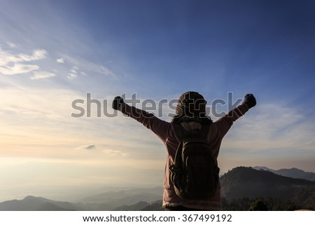 Woman with backpack standing on top of a mountain with raised hands, Successful feeling concept