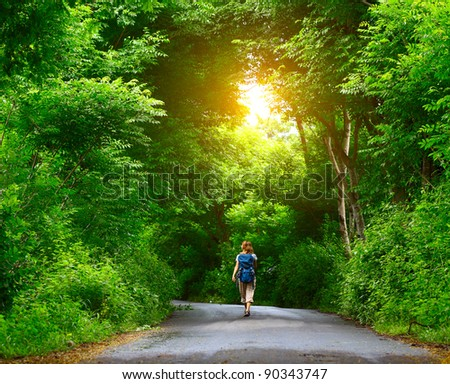 Woman with backpack walking on an asphalt road in a park with green trees - stock photo