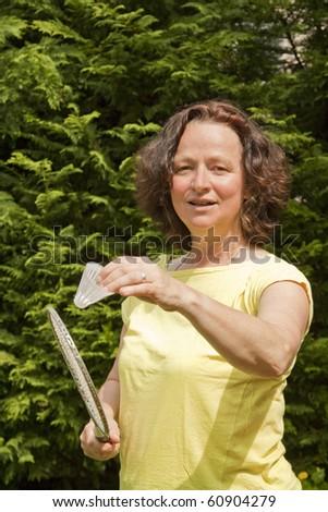 Woman with badminton racket- outdoor shot - stock photo