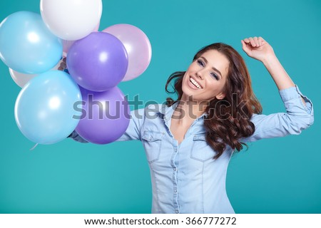 Woman with balloons in studio on a blue background