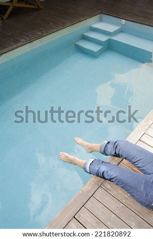 Woman with bare feet in swimming pool - stock photo